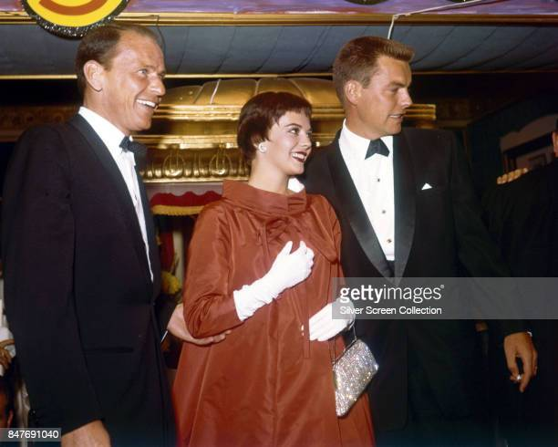American singer and actor Frank Sinatra actress Natalie Wood and her husband actor Robert Wagner smile as they attend the benefit premiere of...