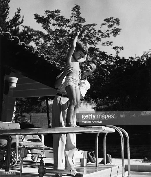 American singer and actor Frank Sinatra holds on to his fiveyearold son Frank Jr who prepares to jump off a diving board into a swimming pool...