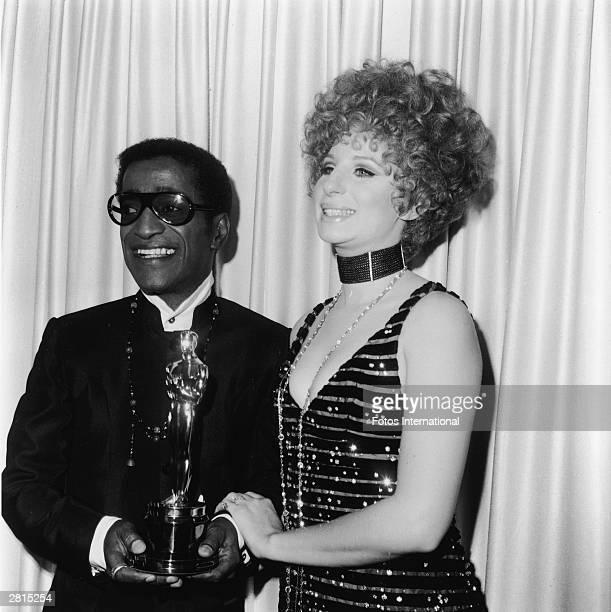 American singer and actor Sammy Davis Jr poses with Barbra Streisand holding the Oscar for Best Song at the Academy Awards ceremony Santa Monica...