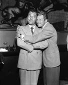 American singer and actor Tony Martin makes a funny face as he receives a warm congratulatory hug from comic actor Danny Kaye at a party shortly...