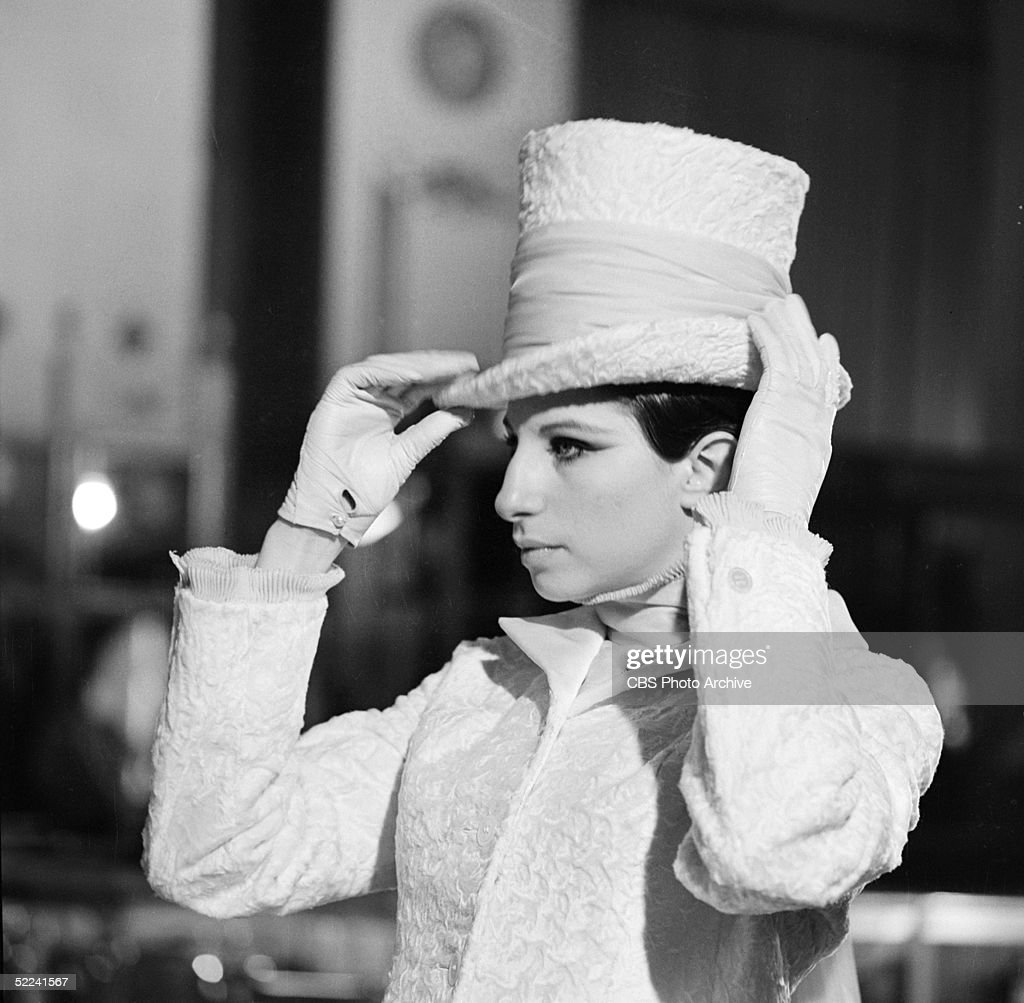 American singer and actress Barbra Streisand adjusts her top hat as she tapes a scene inside the Fifth Avenue department store Bergdorf Goodman for...