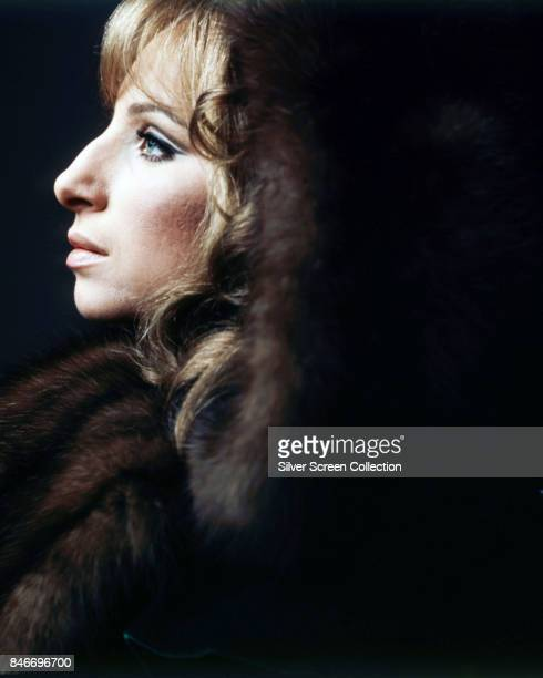American singer and actress Barbra Streisand as she poses wearing a fur coat circa 1970