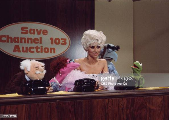 American singer and actress Cher sits behind a desk with from left Mr Waldorf Mildred Huxletter Sam the Eagle and Kermit the Frog all from 'The...