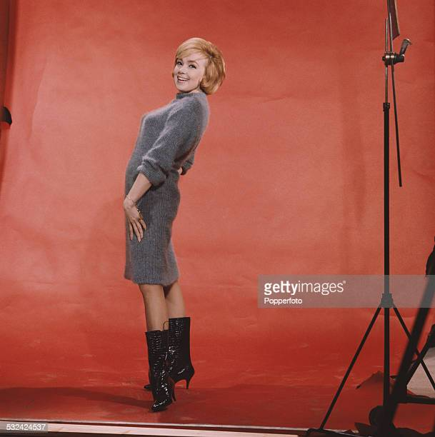 American singer and actress Edie Adams posed wearing a blue knee length woollen dress and black leather boots in a photographic studio in 1962