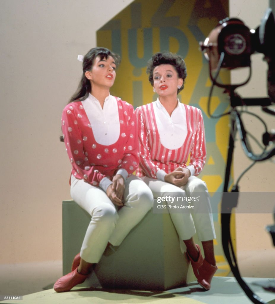 American singer and actress Judy Garland and her daughter singer and actess Liza Minnelli sit together on a stage cube on top of a raised platform...