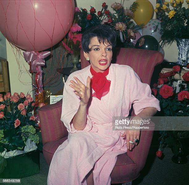 American singer and actress Judy Garland pictured wearing a pink dressing gown and sitting in her dressing room backstage surrounded by bouquets of...