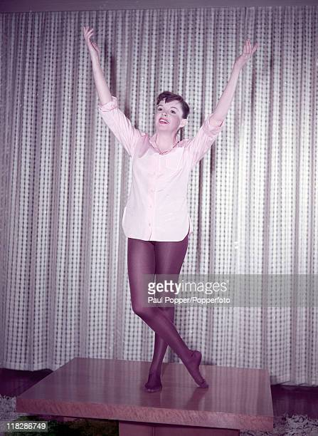 American singer and actress Judy Garland standing on a table in a theatrical pose circa 1960