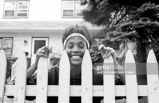 American singer and actress Whitney Houston looks over the picket fence of her mother's home West Orange New Jersey May 28 1985