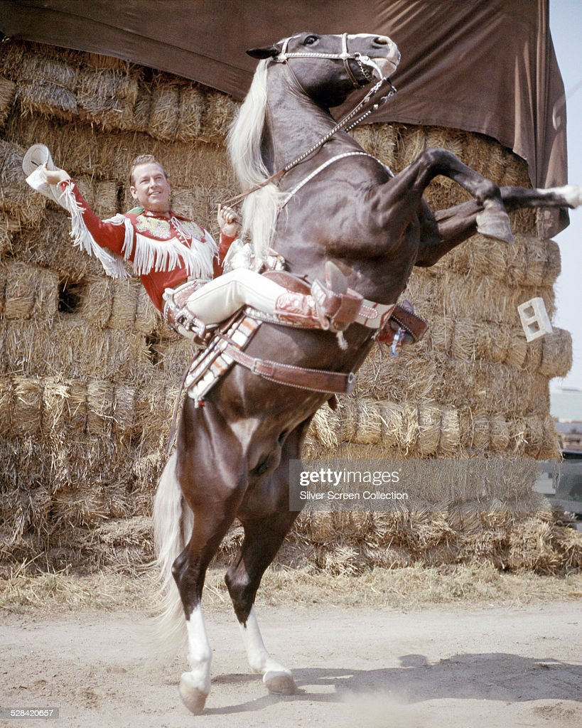 American singer and cowboy actor Roy Rogers on his rearing palomino horse Trigger circa 1950