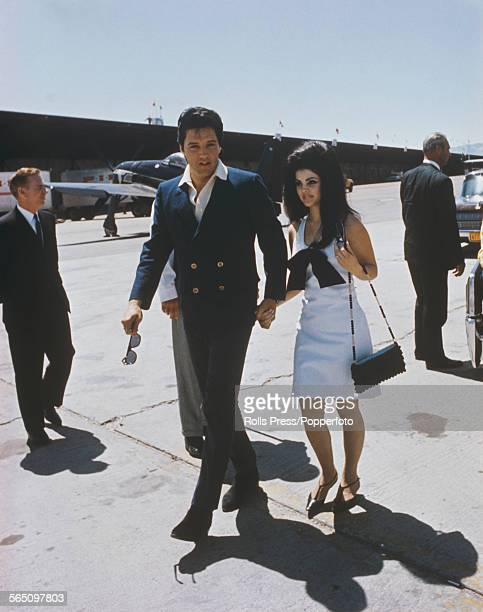 American singer and musician Elvis Presley pictured with his wife Priscilla Presley at an airport during their honeymoon journey from Las Vegas...