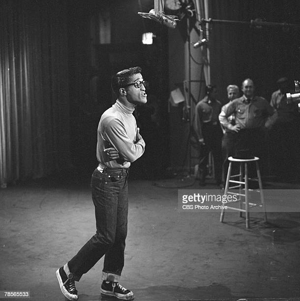 American singer and musician Sammy Davis Jr dressed in jeans hightop tennis shoes and eyeglasses speaks to the camera during the filming of an...