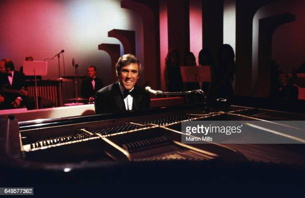 American singer and pianist Burt Bacharach performs with his piano circa 1968 in Los Angeles California