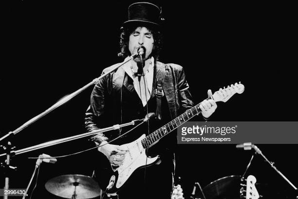 American singer and songwriter Bob Dylan sings and plays guitar on stage wearing a top hat during the Blackbushe Pop Festival Hampshire England July...
