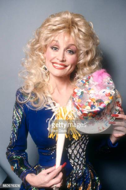 American singer and songwriter Dolly Parton poses for a portrait with a party hat and a party blower for her birthday circa 1990's