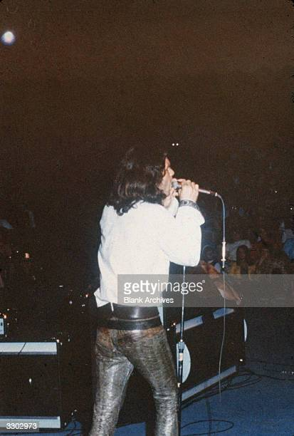 American singer and songwriter Jim Morrison of the rock band The Doors performs onstage wearing a white shirt and leather pants