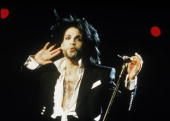 American singer and songwriter Prince stands on stage with a microphone one hand by his ear to hear the crowd response during a concert February 1991