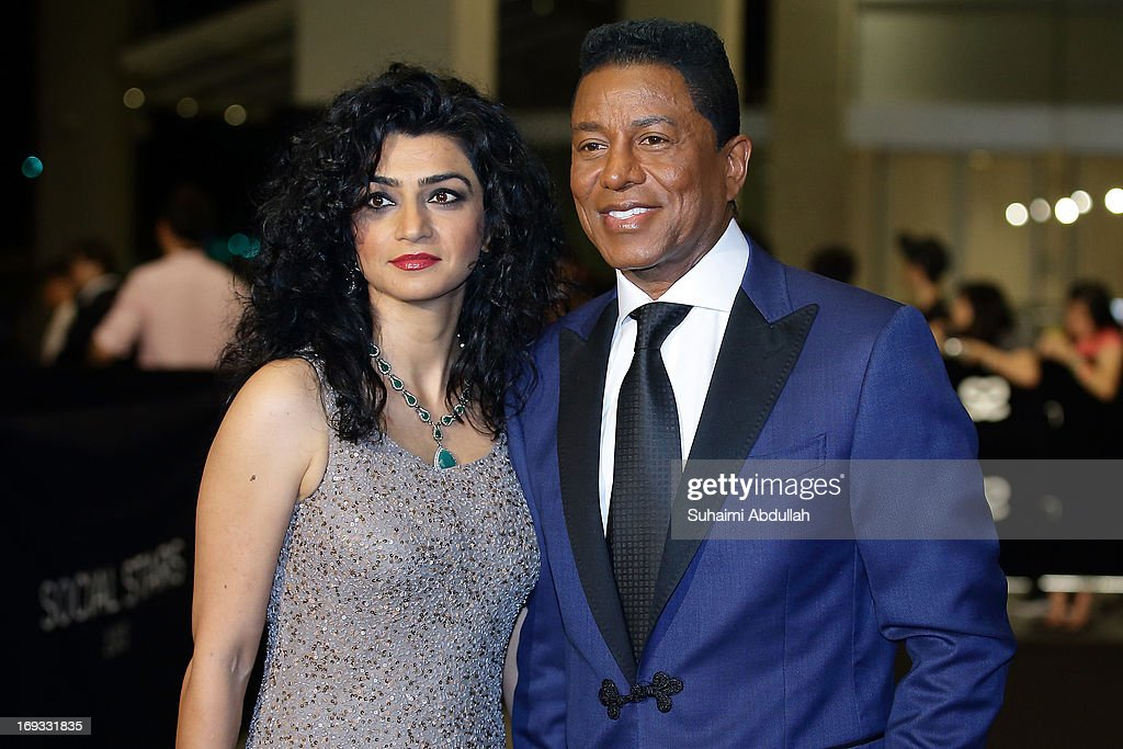 American singer, bass guitarist, composer, member of The Jackson 5, Jermaine LaJuane Jacksun (R) walks the red carpet with a guest during the Social Star Awards 2013 at Marina Bay Sands on May 23, 2013 in Singapore.