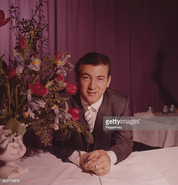 American singer Bobby Darin pictured sitting at a table in London in 1963
