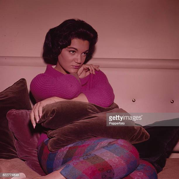 American singer Connie Francis posed wearing a pink jumper and striped trousers in London in 1963