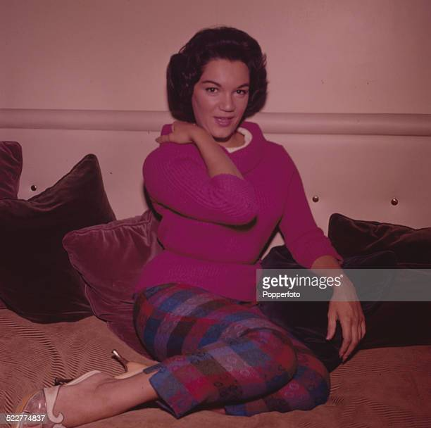 American singer Connie Francis posed wearing a pink roll necked jumper and checked capri trousers in London in 1963