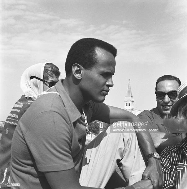 American singer Harry Belafonte sitting on a floor among others Venice 1958