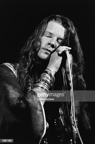 American singer Janis Joplin closes her eyes and cradles a microphone while performing c 1967