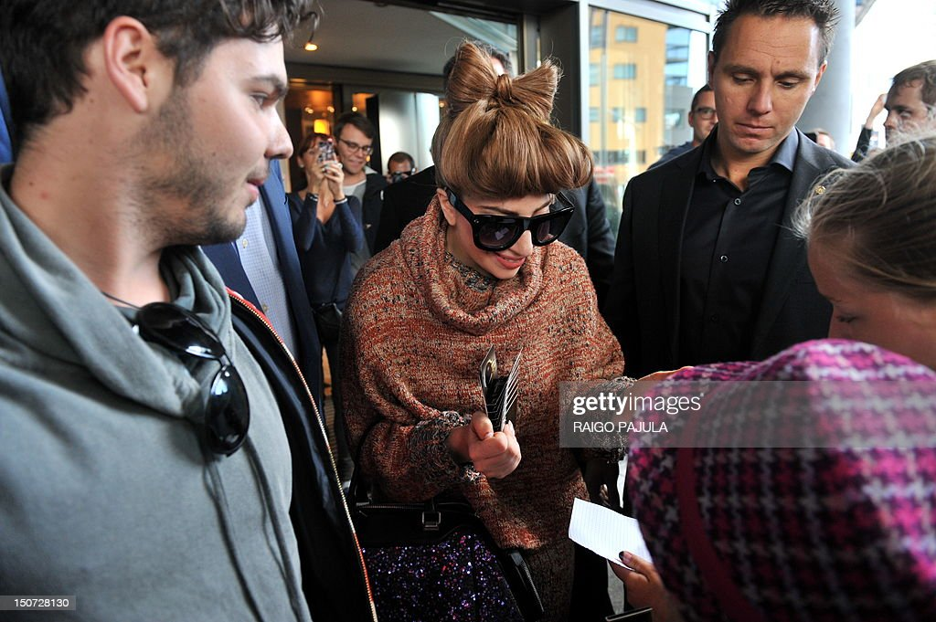 American singer Lady Gaga (c) sign autographs for fans as she leaves her hotel on August 25, 2012 in Tallin, where she is to give a concert as part of her European tour.