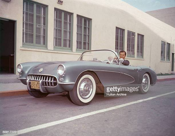 American singer Pat Boone sits in his 1956 or 1957 Chevrolet Corvette sports car and smiles late 1950s