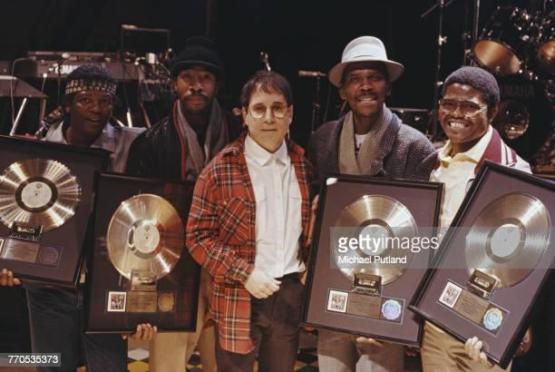 American singersongwriter Paul Simon of folk rock duo Simon Garfunkel posed with four musicians all holding gold discs of Paul Simon's album...