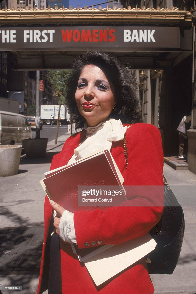 American social activist and banker Alice Heyman stand sin a red jacket and holds dosuments on the sidewalk outside the First Women's Bank, which she co-founded, East 57th Street, Manhattan, New York, 1980s. The bank, founded in 1975, was sold and its name changed (to First New York Bank for Business) in 1989 and it closed forever in 1992.