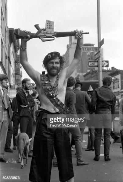 American social and political activist Jerry Rubin stands shirtless as a he holds an M16 assault rifle above his head at the intersection of St Marks...