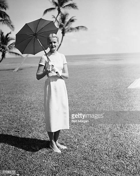 American socialite CZ Guest poses with an umbrella in Palm Beach Florida 1954
