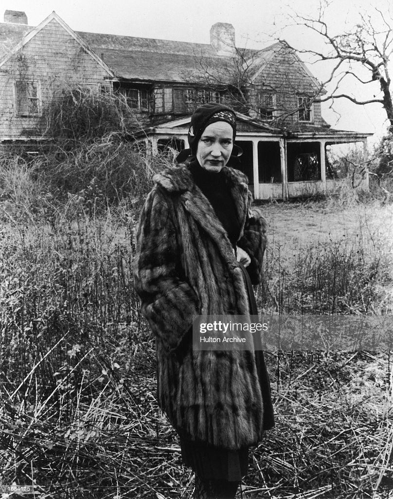 American socialite Edith Beale Jr. (1917 - 2002) wears a fur coat while posing in front of her dilapidated East Hampton, Long Island, mansion in a still from the documentary film, 'Grey Gardens,' directed by Ellen Hovde, Albert and David Maysles and Muffie Meyer, 1975.