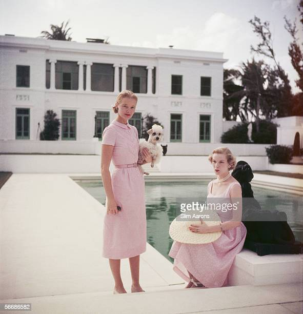 American socialite Mrs Winston F C Guest poses with Joanne Connolly beside the Grecian temple pool of her oceanfront estate Villa Artemis in Palm...