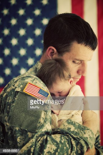 American soldier holding a newborn baby