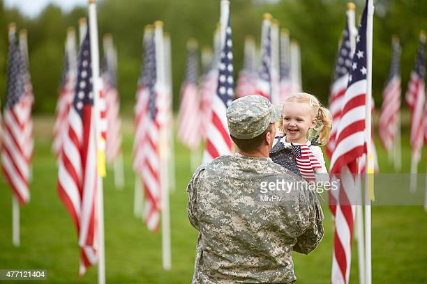 American soldier holding his happy toddler daughter