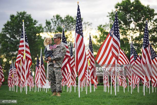 American soldier holding his toddler daughter