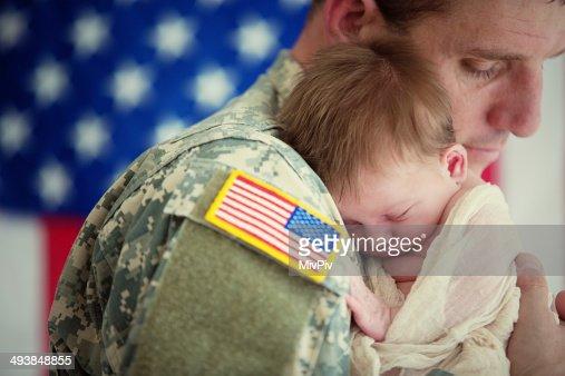 American soldier holding newborn baby