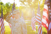 American Soldier saluting in front of American flags in the sunset