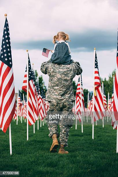 American soldier walking with his daughter on his shoulders
