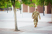 US soldier in front of campus holding books.