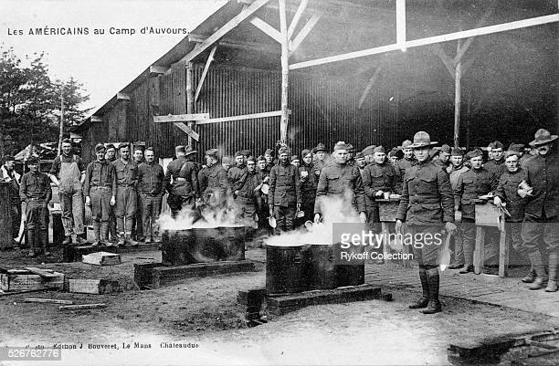 American soldiers at Camp d'Auvours stand in line for chow served from several large streaming buckets | Located in Rykoff Collection