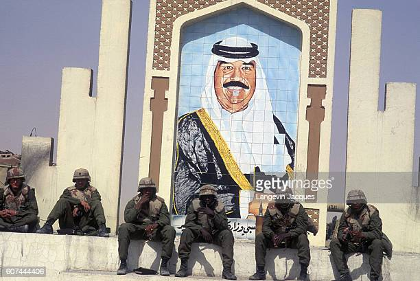 American soldiers deployed in Kuwait during the Persian Gulf War rest in front of a mural of Saddam Hussein In August of 1990 Iraqi president Saddam...