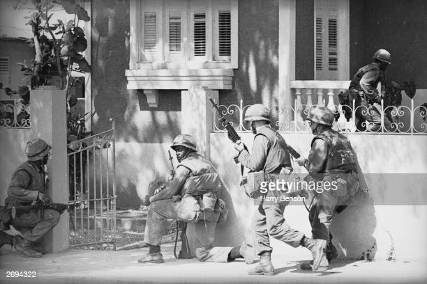 American soldiers entering a house while stationed in Dominica during the civil war which led to the island becoming an internally selfgoverning...