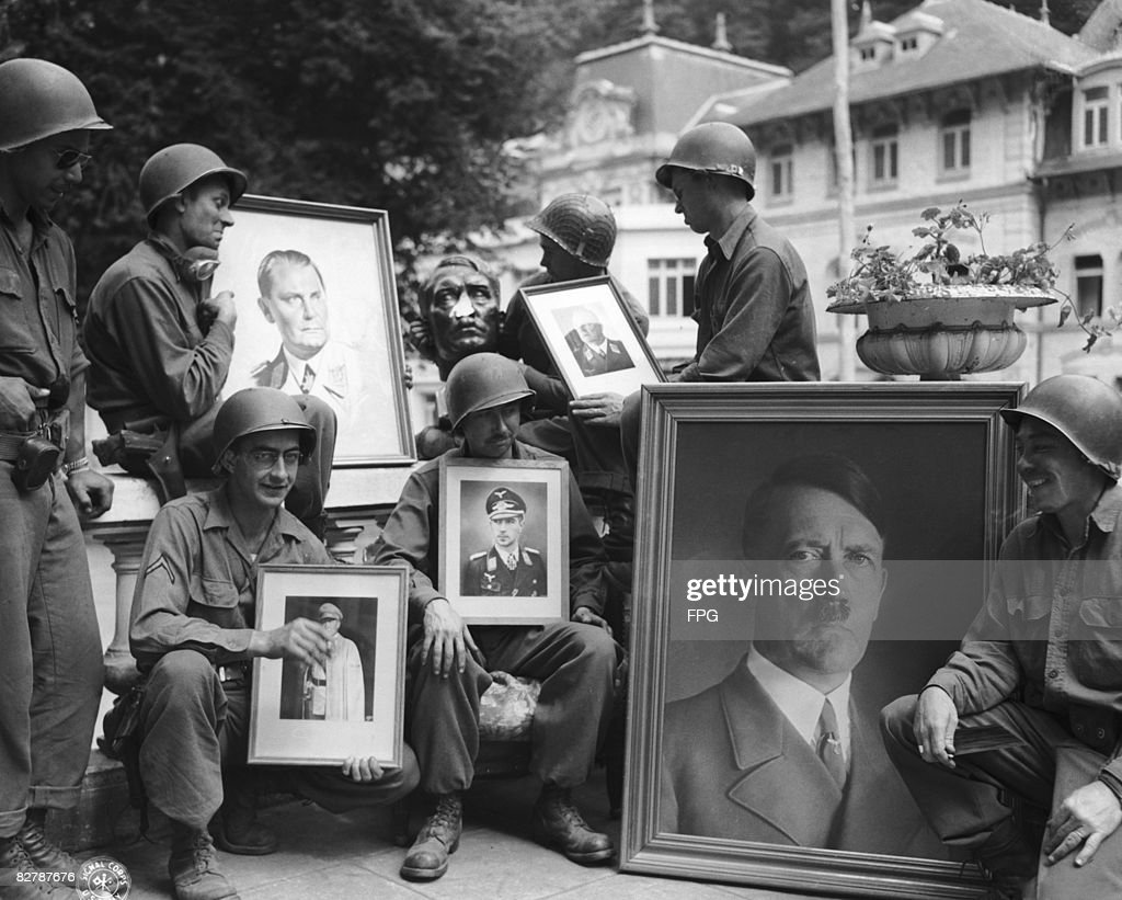 American soldiers hold up pictures of high-ranking Nazi officials discovered in a French hotel formerly occupied by the Germans, 15th August 1944. Front, from left to right, the soldiers are Sergeant W. F. Lovell, Private Hoover, Lieutenant Amos Potts Jr. and PFC Howard Burns. Back, left to right, Sergeant Aloysius Unsen, PFC Charles E. Law and Private Donald Sykes.