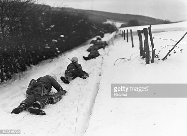 American soldiers of the 2nd Infantry Division lie flat in the snow to escape enemy machinegun fire during the Battle of the Bulge Near Ondenval...