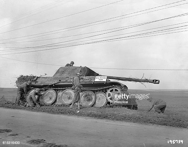 American soldiers of the Fifth Division inspect a German Mark V Panther tank by the side of a road