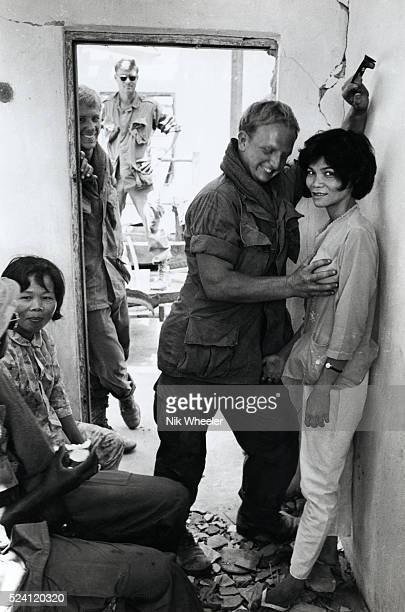 American soldiers play with Vietnamese prostitutes in ruins of bombed village during an operation outside Saigon during the Vietnam War in South...