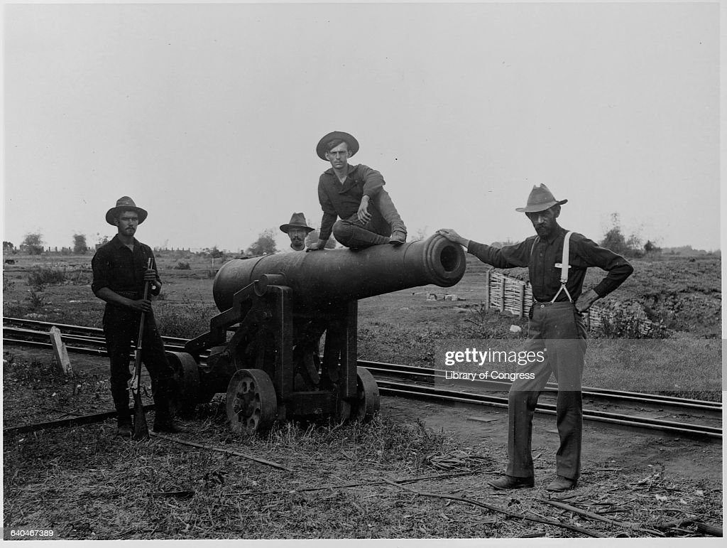 American soldiers pose next to a captured cannon during the Philippine Insurrection an uprising in response to America's colonization of the area...