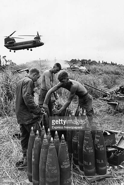 American soldiers priming shells on Hill Timothy Vietnam A Chinook helicopter flies in the background